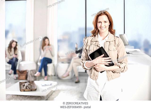 Portrait of smiling woman holding digital tablet