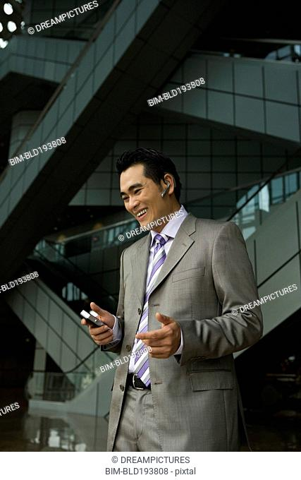 Chinese businessman talking on cell phone with hands-free device