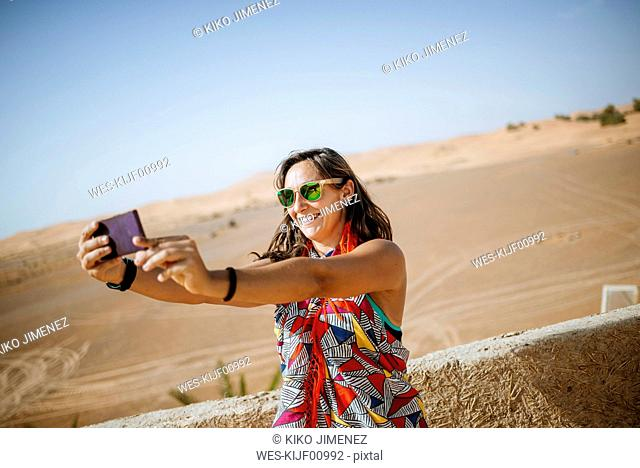 Morocco, Merzouga, smiling torist taking selfie with smartphone