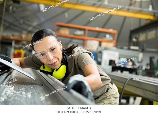 Worker examining sheet metal in manufacturing plant