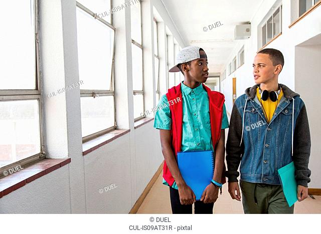 Students walking down hallway, chatting