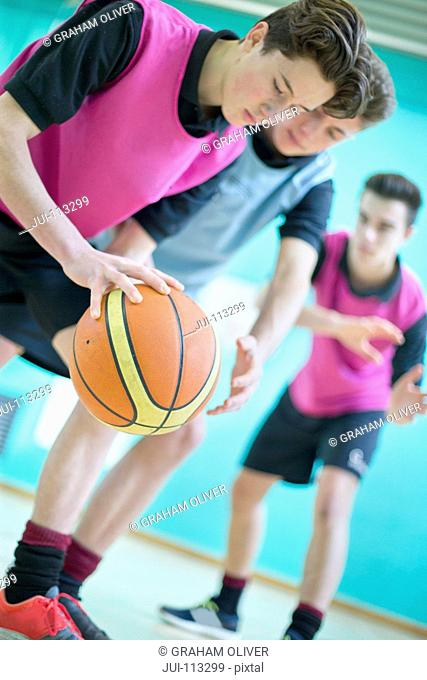 High school students playing basketball in gym glass