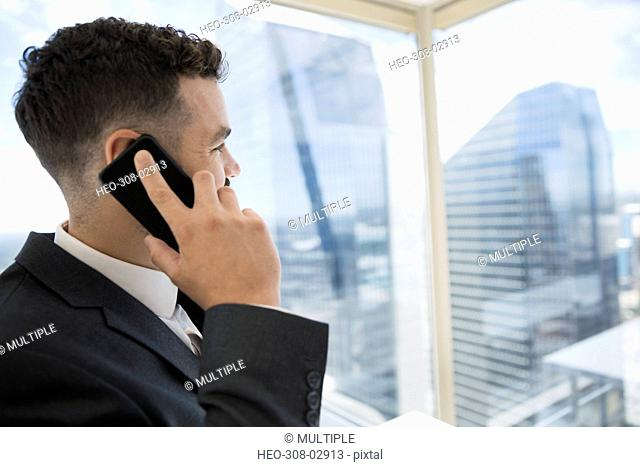 Businessman talking on cell phone at urban office window