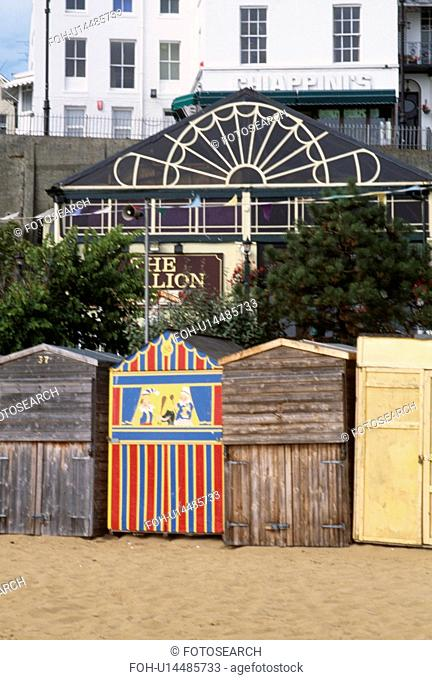 Wooden beach huts with painted Punch & Judy hut on the beach at Broadstairs in Kent