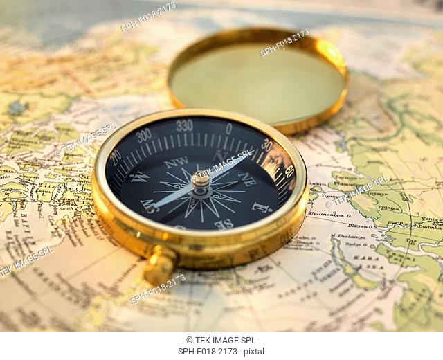 Compass sitting on a map of the artic circle