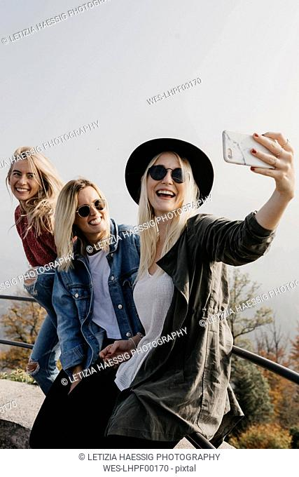 Germany, Black Forest, Sitzenkirch, three happy young women taking a selfie at Sausenburg Castle