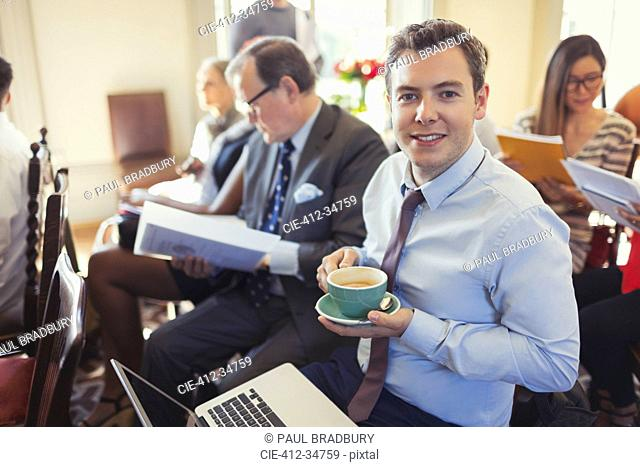 Portrait smiling businessman drinking coffee and using laptop in business conference audience