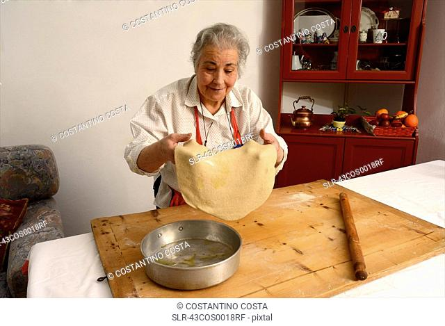 Older woman stretching sheet of dough