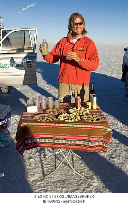 Man serving drinks on the Salar de Uyuni, Bolivia
