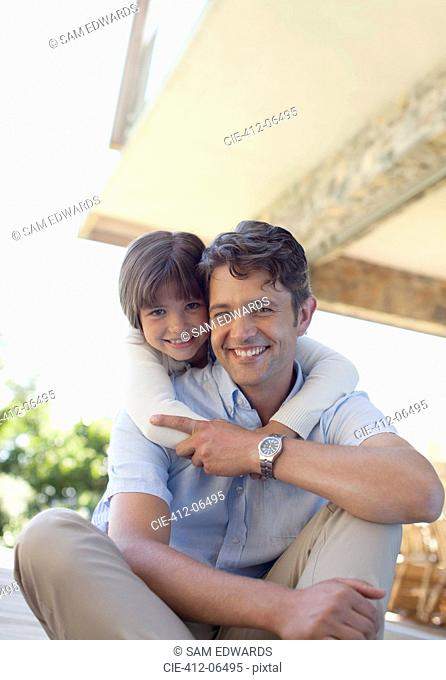 Father and daughter sitting together outdoors