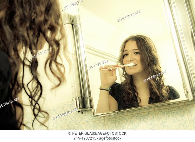 Teenage girl brushing her teeth