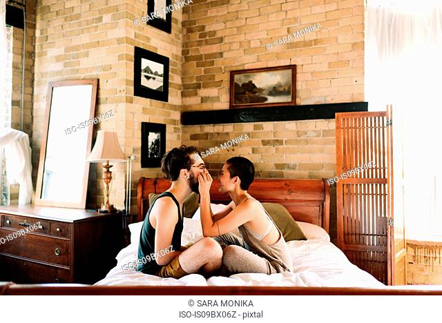 Couple sitting cross legged on bed