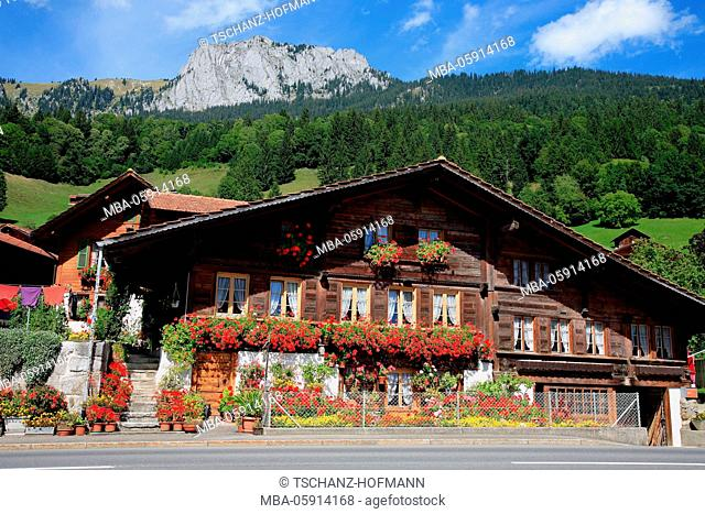 Old Simmentaler farmhouse with floral decoration, close Erlenbach at the Simmental, the Bernese Oberland, Switzerland