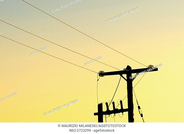 Diagonal Power line on wooden poles in silhouette at sunset
