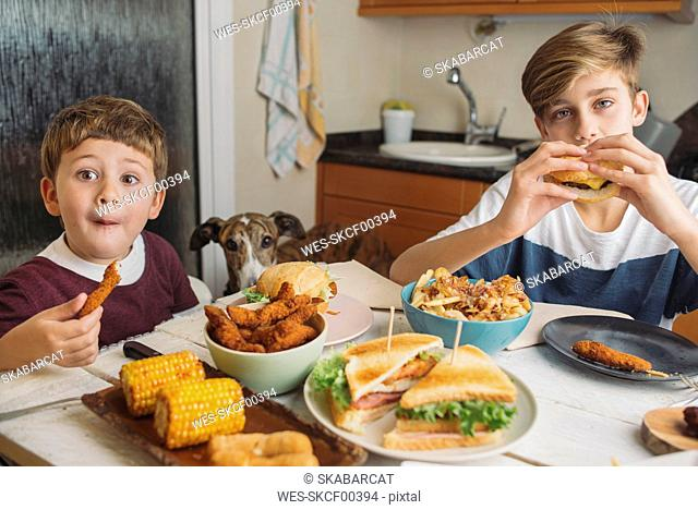 Two boys with dog enjoying american food at dining table at home