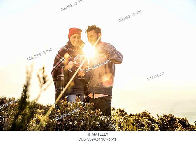 Couple in field pouring wine