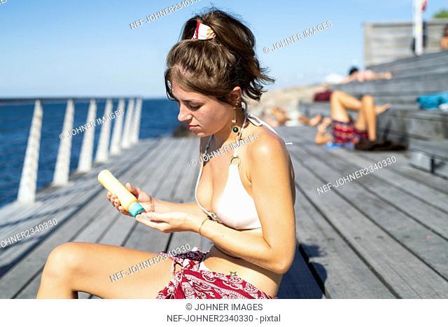 Young woman applying sun protector