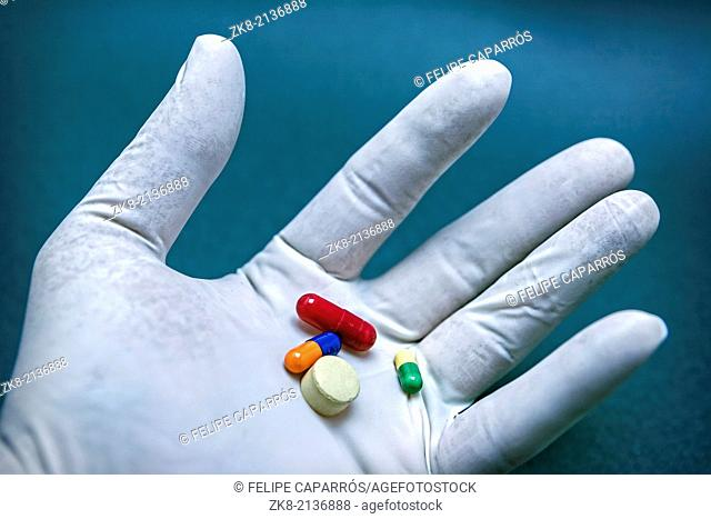 Hand with white latex glove turning various pills