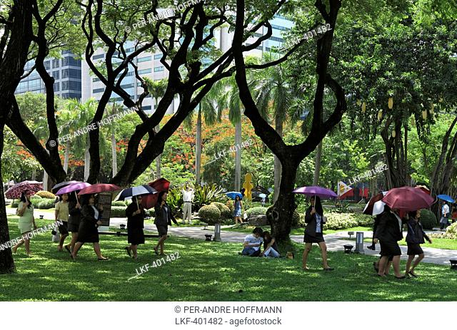 Women with umbrellas, Ayala Triangle Park in Makati City, Luzon Island, Philippines, Asia