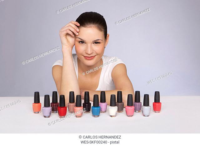 Young woman with nail polish bottles, portrait