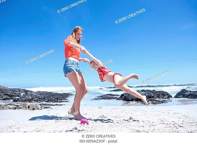 Young woman holding and spinning girl on beach, Cape Town, South Africa