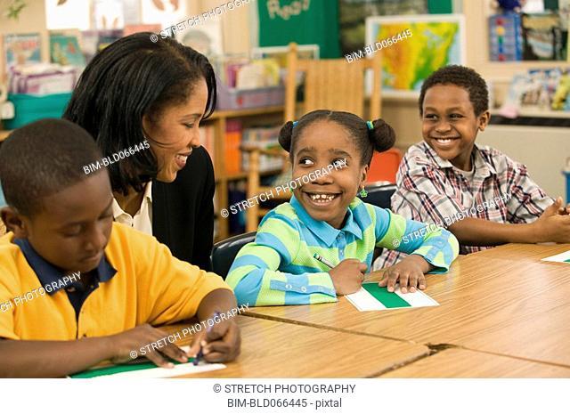 African school teacher helping students