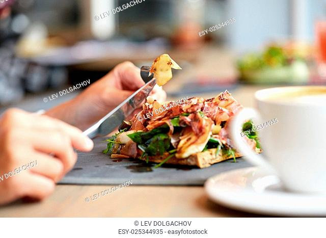 food, dinner and people concept - woman eating prosciutto ham salad on stone plate at restaurant