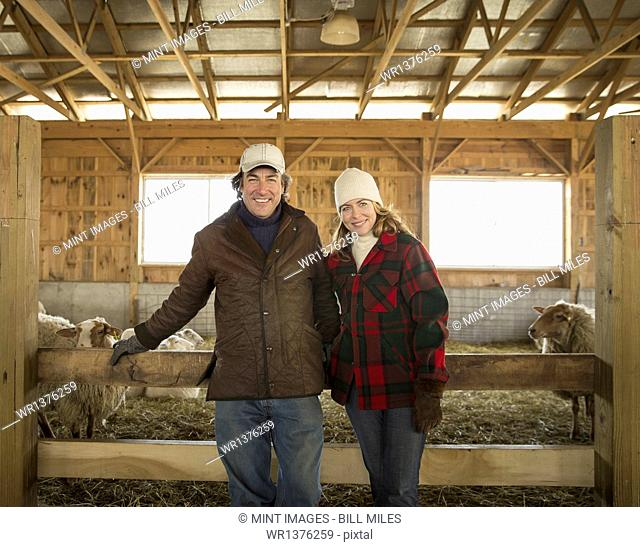An Organic Farm in Winter in Cold Spring, New York State. A farmer and a woman standing by a pen full of sheep