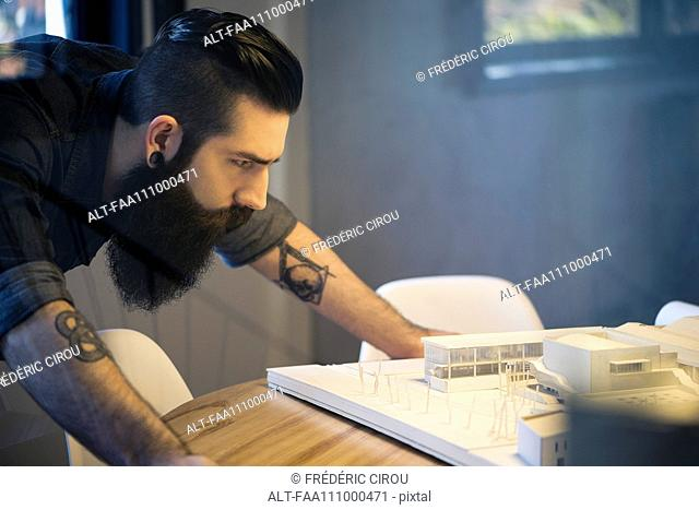 Man looking at model building in office