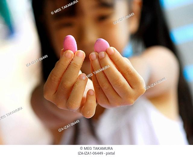 Close-up of a girl's hands showing candies