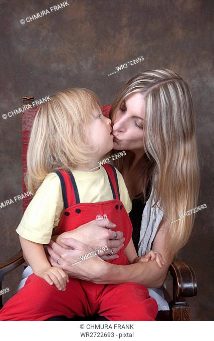 mother and son both with long blond hair, kissing