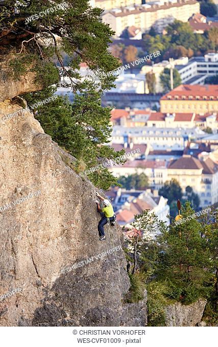Austria, Innsbruck, Hoettingen quarry, man climbing in rock wall