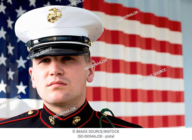 Serviceman in dress blues by US flag