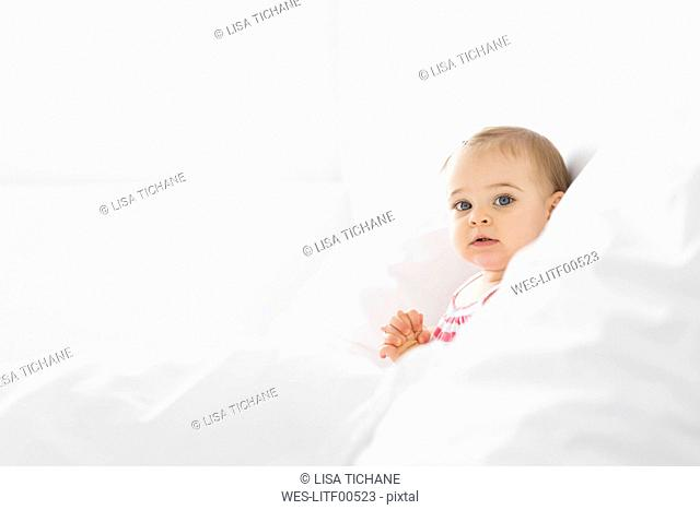 Portrait of baby girl sitting on a white bed between pillows