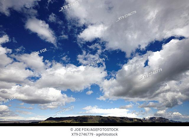 white clouds in blue sky over open farmland in southern Iceland