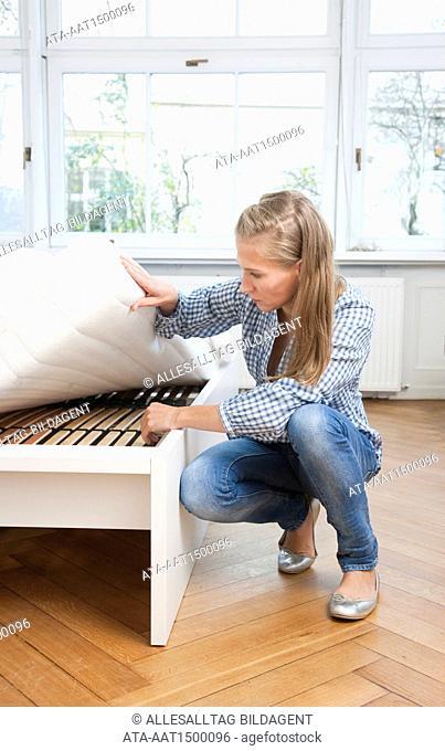 Woman raising mattress