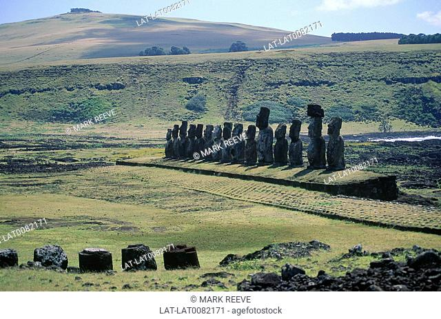 Rano Raraku. Giant moai/ stone heads and torsos in line. Some with headdresses. Cobbled path. Hills
