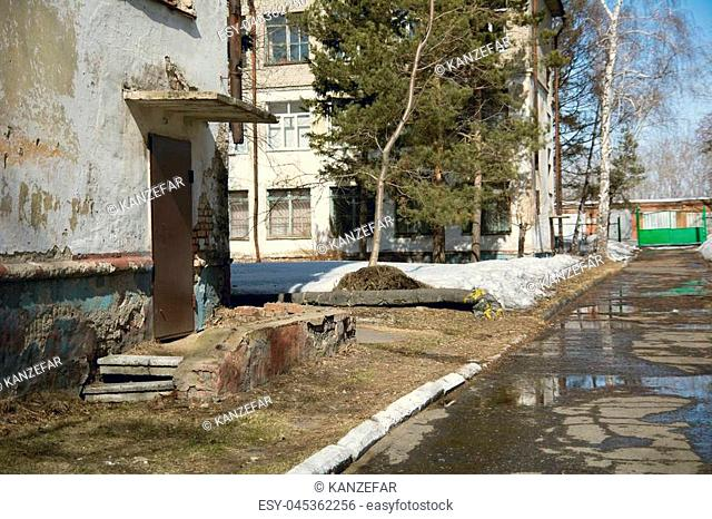 Old building in sunny weather with spring puddles and snow. Background part of a house with ruined walls
