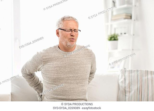 unhappy senior man suffering from backache at home