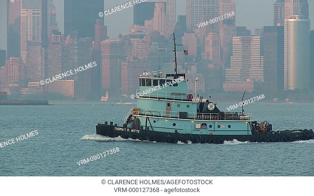 NEW YORK - SEPTEMBER 11: Donjon Marine tugboat Thomas D. Witte works the waters of New York Harbor, with the Statue of Liberty and buildings of lower Manhattan...