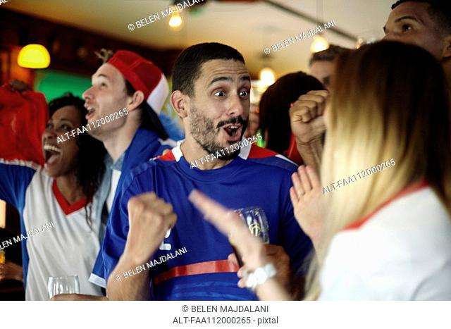 French football fans celebrating victory in bar