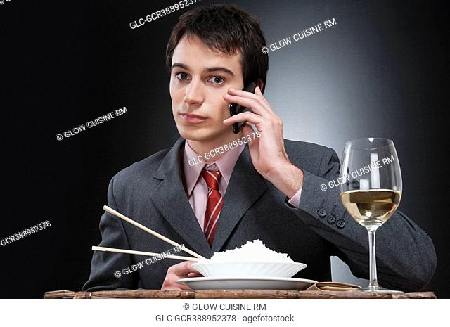 Businessman talking on a mobile phone while eating