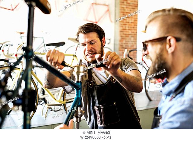 Two men in a cycle repair shop, looking at a bicycle