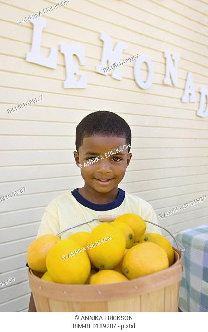 Mixed race boy holding basket of lemons