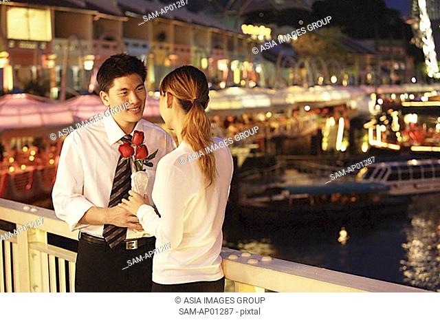 Man and woman standing face to face, woman holding roses
