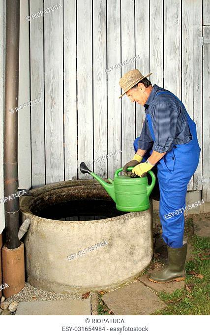 A Gardener next to his Rain water barrel