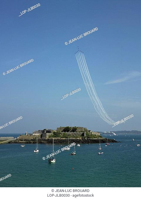 England, Channel Islands, Guernsey, A Red Arrows display team fly in formation over Castle Cornet in Guernsey