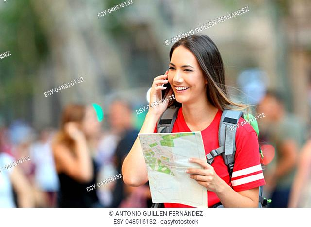 Happy teen tourist talking on phone holding a map walking on the street