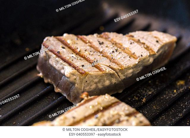 Close up of chargrilled tuna steaks cooking in a griddle pan with seasoning