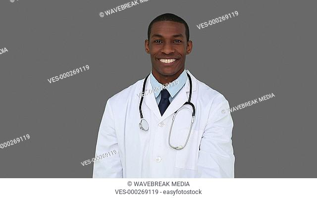 Happy young doctor showing camera an apple